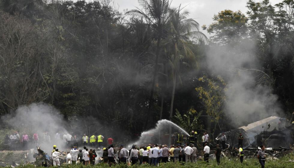 STYRT: Brannmannskaper slukker flammer fra passasjerflyet som styrtet i Havanna i Cuba fredag. Foto: Enrique de la Osa / AP / NTB scanpix