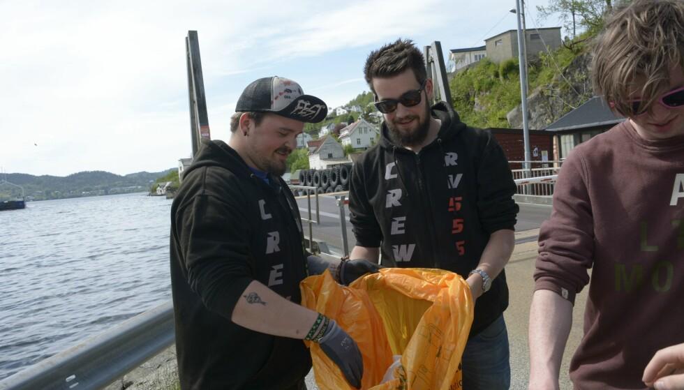 RYDDER: Joakim Tverlid Andersen (t.v.), Andreas Tokheim og Tormod Lavik plukker søppel ved Valestrand kai på Osterøy. Foto: Anders Totland / Bygdanytt