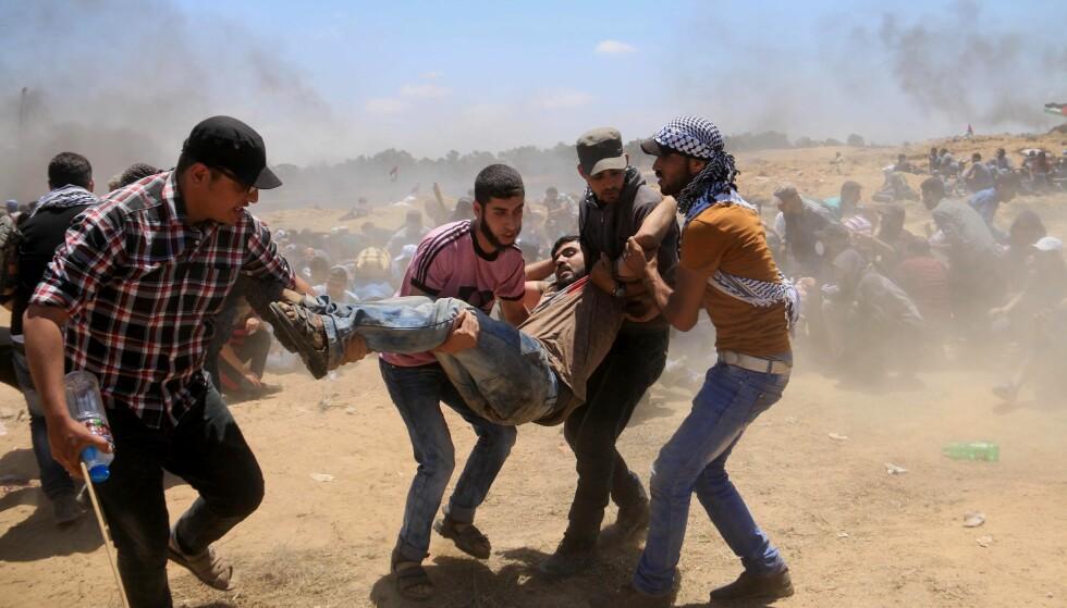 BLODIG: En skadet palestinsk demonstrant blir evakuert under sammenstøtene med israelske sikkerhetsstyrker forrige mandag. Minst 55 palestinere ble drept av israelske soldater demonstrasjonene, på det som var den blodigste dagen på Gazastripen siden 2014-krigen med Israel. Foto: APAImages / REX / Shutterstock / NTB scanpix