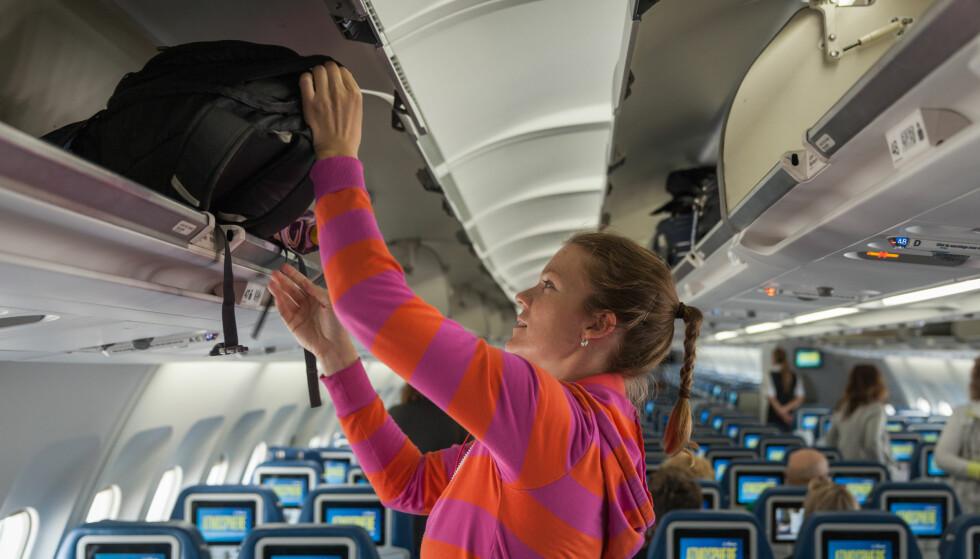 FULLE HYLLER: At det medbringes mye håndbagasje inn i flyene er udiskutabelt. I en ny rapport foreslås det at hattehyllene skal låses under avgang og landing for å forhindre at passasjerene prøver å få med seg kabinbagasjen ut ved eventuelle evakueringer. Foto: Shutterstock / NTB Scanpix