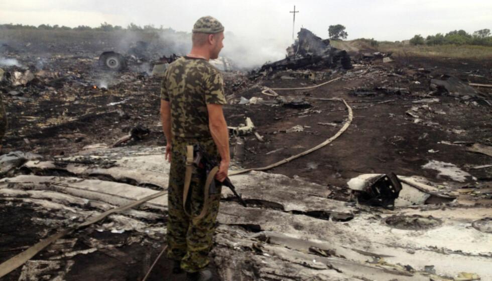 KATASTROFE: En prorussisk opprører betrakter vraket av MH17 etter nedskytingen 17. juli 2014. Foto: Maksim Zmejev / Reuters / NTB Scanpix