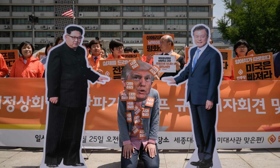 SPILLET: Fra en demonstrasjon i den sør-koreanske hovedstaden Seoul. Kim Jong-un, Donald Trump, på kne, og Sør-Koreas president Moon Jae-in. Foto: AP / NTB Scanpix