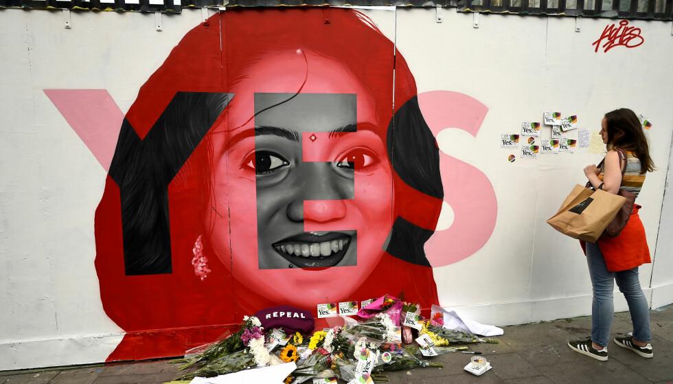HISTORISK: Folkeavstemningen i dag er historisk. Avbildet på veggen er Savita Halappanavar, som døde av betennelse i fosteret og morkaka i 2012 fordi hun ikke fikk lov til å ta abort. Foto: Clodagh Kilcoyne / Reuters / NTB Scanpix