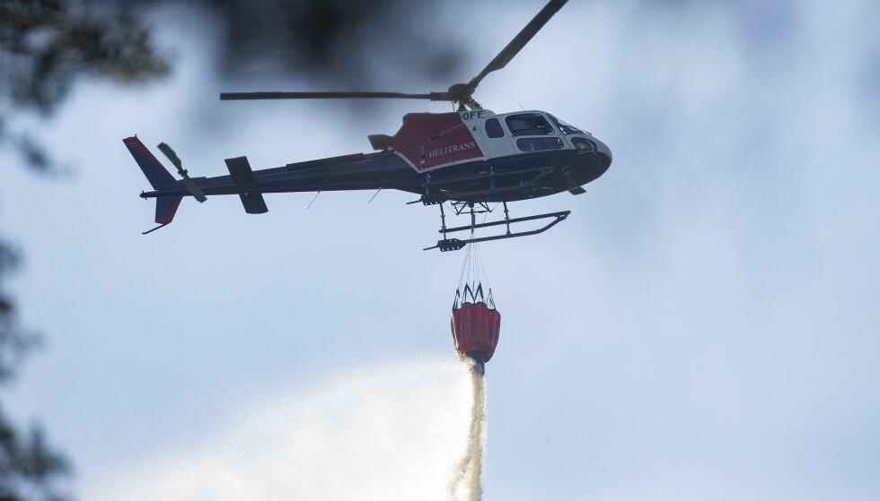 BRANNER: Brannvesenet har rykket ut til hele 343 branner i inn- og utmark i mai. Selv om det er langt igjen til årsrekorden for 2014, bes folk om å være forsiktige. Et vanningshelikopter prøver å slukke deler av skogbrannen i Lommedalen etter den ekstreme hetebølgen. Foto: Fredrik Hagen / NTB scanpix