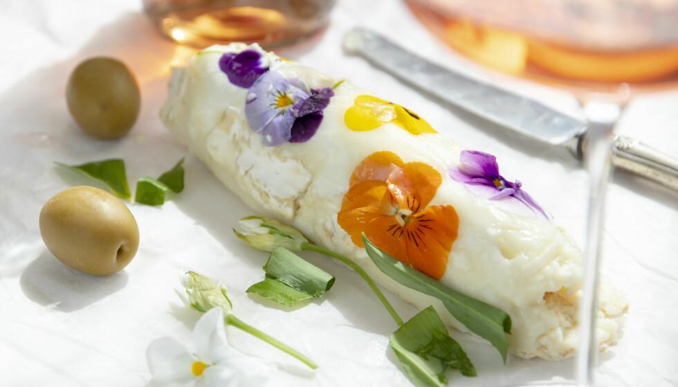 GODT FØLGE TIL ROSÉ: Ta 150 g chevre, 2 ss olivenolje og noen spiselige blomster. Mos ca 150 g chevre og 2 ss olje sammen. Bruk bakepapir og form til en pølse. Legg på de spiselige blomstene og klem dem inn i osten. Skjær i skiver og spis, eventuelt med litt brød og noen oliven. Foto: Lisbeth Michelsen