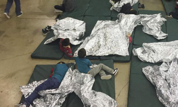 LEIRE: På dette bildet, sluppet av USAs grensevakt, er en rekke barn plassert i det som kalles bur. Rommet er inngjerdet med metallgjerde og barna har fått utdelt rompledd for å holde varmen. Foto: Grensevakta / Ap