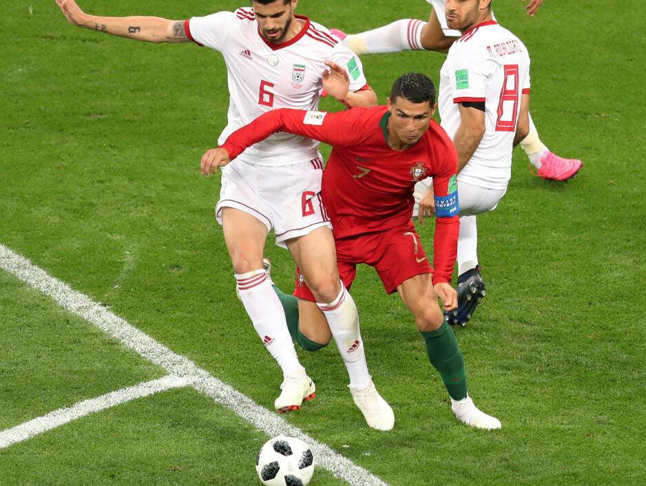 FØRE VAR: Christiano Ronaldo felles i straffefeltet av Irans Saeid Ezatolahi. Etter å ha konsultert videodømmingssystemet VAR, valgte dommeren å dømme straffe. Videodømmingssystemet spilte en avgjørende rolle under de avsluttende gruppespillskampene i går. Foto: REUTERS/Lucy Nicholson  TPX