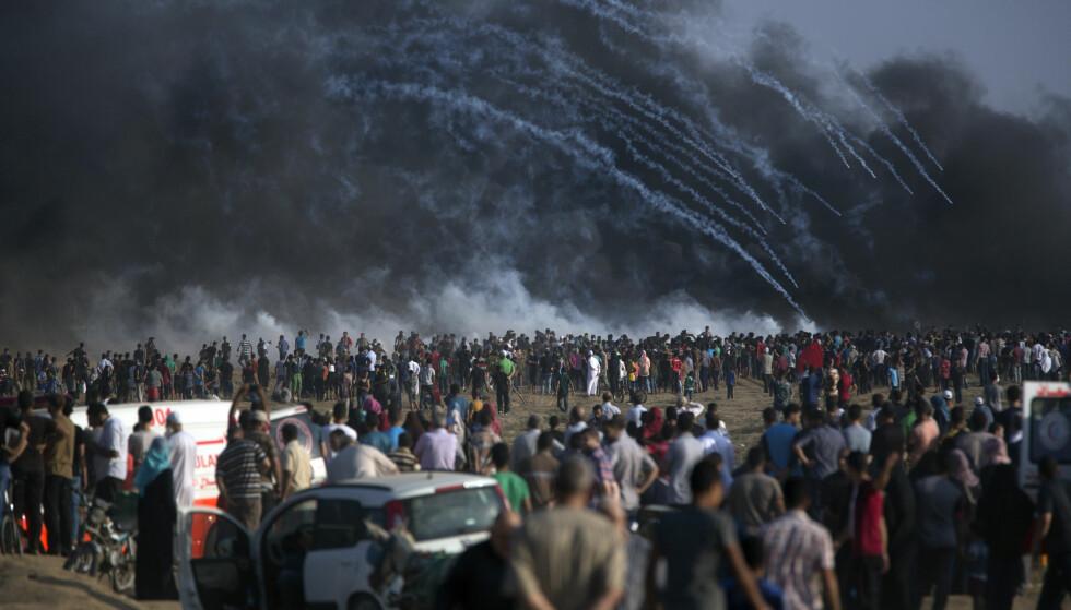 DEMONSTRASJONER: Israelske soldater skjøt tåregass mot demonstrantene under fredagens demonstrasjoner. En 15 år gammel gutt ble drept da han prøvde å klatre over grensegjerdet. Foto: AP / NTB scanpix