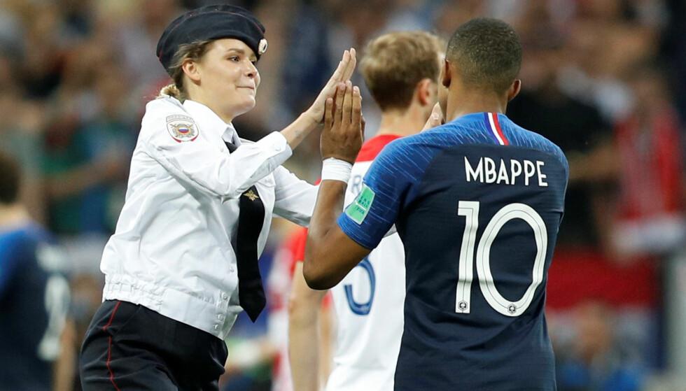 IKONISK: Pussy Riots Veronika Nikulshina fikk en dobbel high five fra Frankrikes unge stjerne Kylian Mbappe da aktivistene stormet banen under VM-finalen søndag. REUTERS/Darren Staples