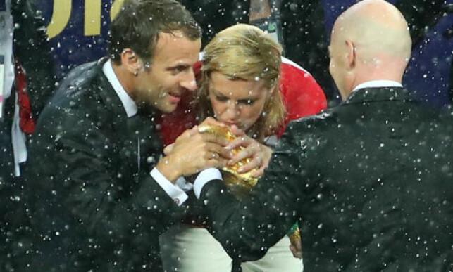 KONTROVERSIELT: Emmanuel Macron har akkurat kysset VM-pokalen. Rett etterpå gjør Kolinda Grabar-Kitarovic det samme, selv om hun representerer det tapende laget. Foto: NTB scanpix