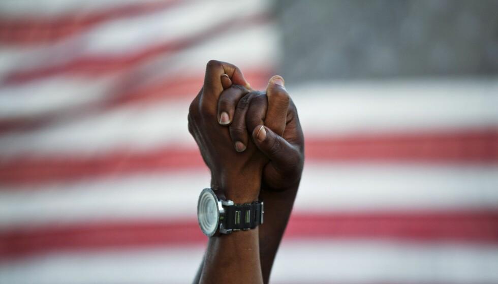 USA: «America is broken», skriver John Freeman i forordet til boka «Tales of Two Americas». Bildet er fra en markering etter at en rasistisk motivert skyting på en kirke i byen Charleston drepte ni svarte amerikanere i 2015. FOTO: AP Photo/David Goldman /NTB Scanpix