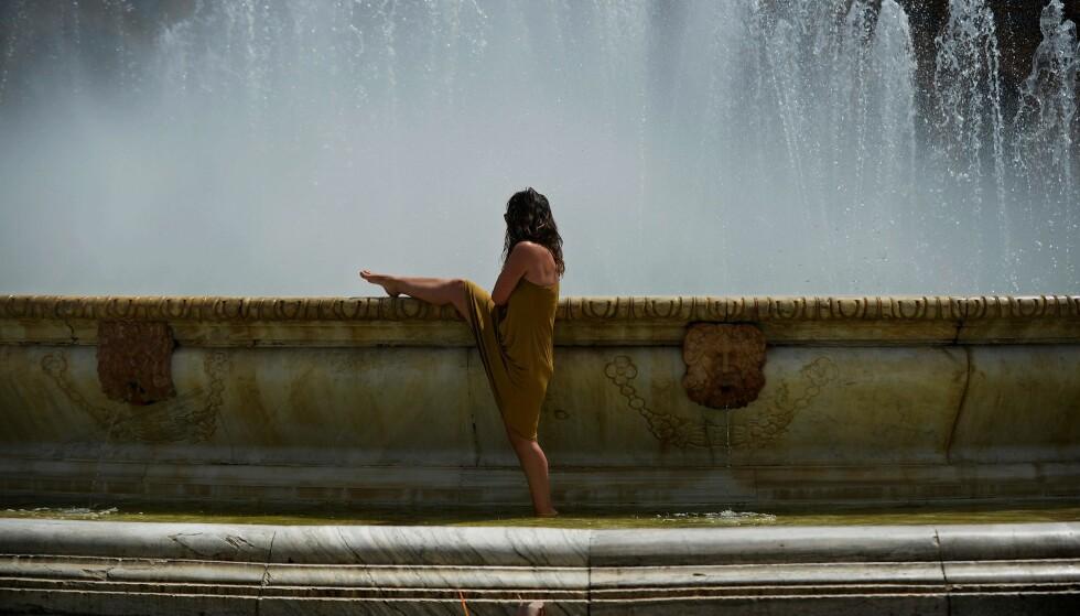 KJØLER SEG NED: En kvinne kjøler seg ned i en fontene på Plaza de Espana i Sevilla onsdag. Mot helga er det ventet mellom 40 og 50 varmegrader i Spania. Foto: Cristina Quicler / NTB Scanpix
