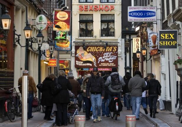 RED LIGHT DISTRICT: Reklameskiltene forteller sitt tydelige språk om hva som foregår i disse gatene i Amsterdam. Foto: NTB Scanpix