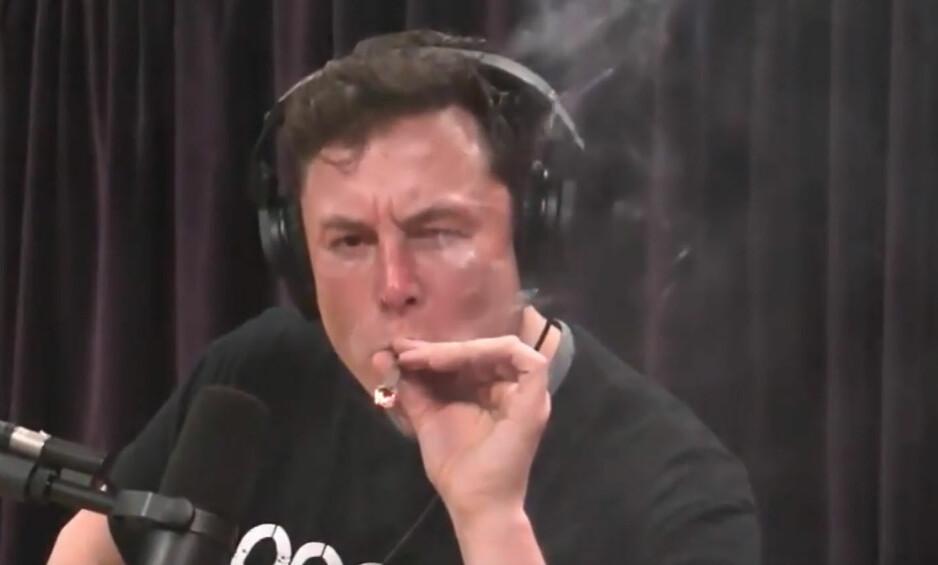 RØYKER: Tesla-sjef Elon Musks røykte det som skal ha vært en marihuana-sigar i et intervju sendt torsdag kveld. Dagen etter stupte aksjen. Foto: NTB scanpix