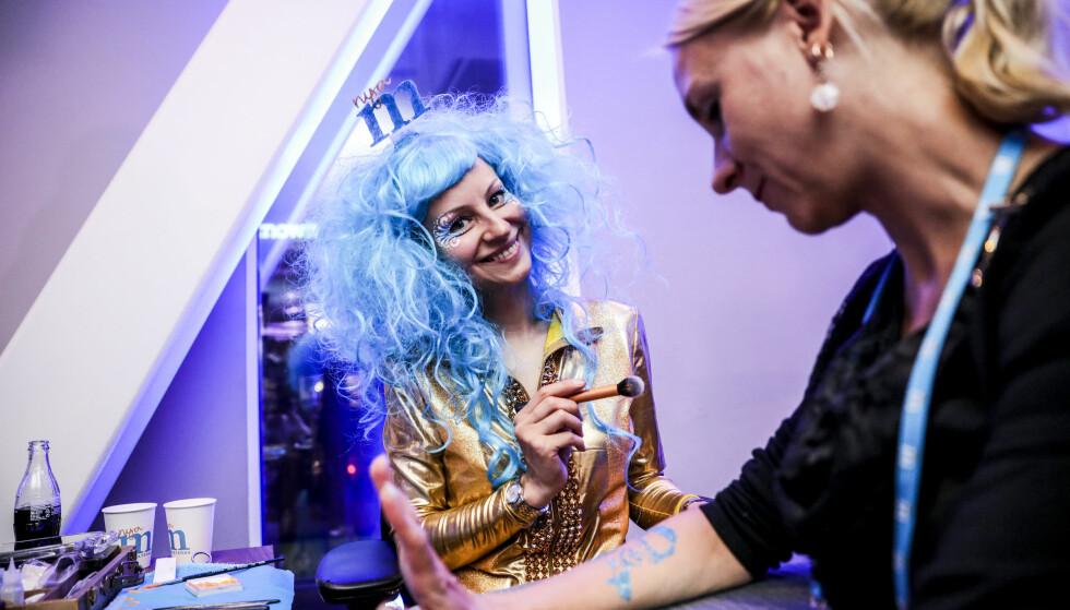 BLÅTT: Kroppsmaler Evgenia (37) maler lyseblå M-er og portrett av partileder Ulf Kristersson på armer og kinn på de som ønsker. Foto: Christian Roth Christensen / Dagbladet
