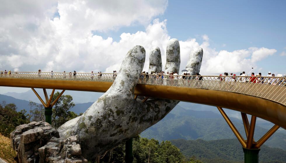 POPULÆR: De nye gangbrua holdes oppe av to menneskehender, og har på kort tid blitt en populær attraksjon. Høyt over tretoppene får turistene flott utsikt til naturen i Ba Na-fjellene. Foto: Reuters / NTB Scanpix