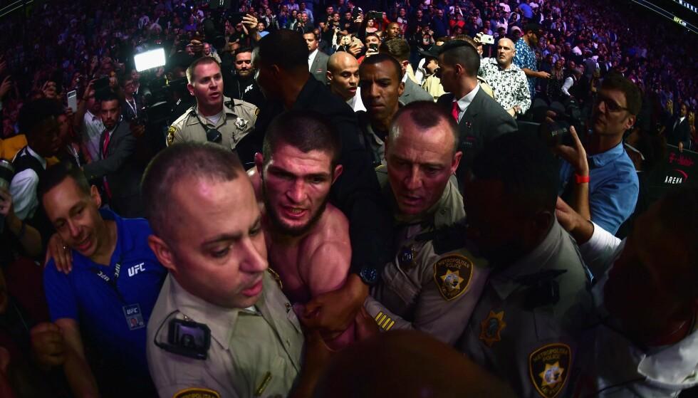 SKANDALEN: Khabib Nurmagomedov blir eskortert ut av hallen av Las Vegas-politi etter at skandalen var et faktum. Foto: Getty Images / NTB Scanpix