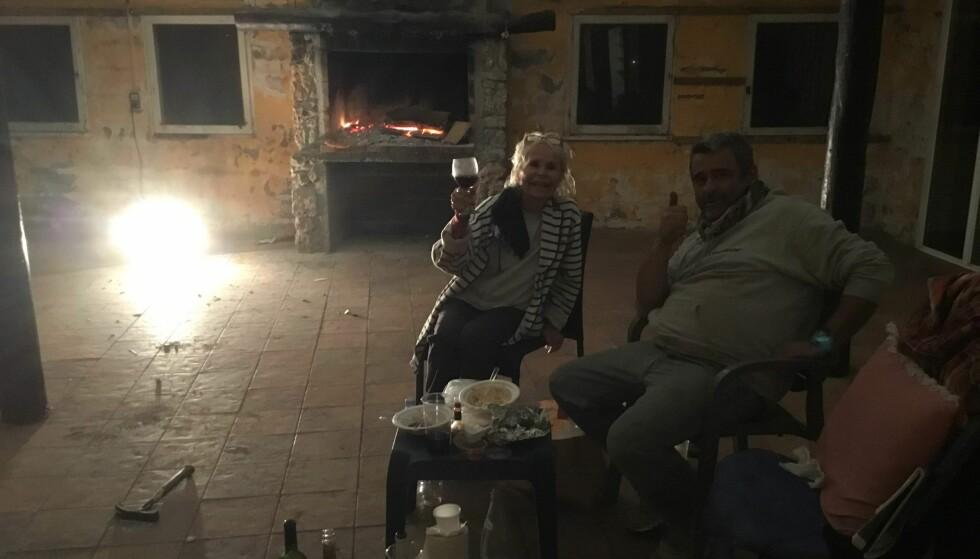 EN SISTE SKÅL - FOR NÅ: Edna Falao og sønnen Manuel er fast bestemte på å bygge ny restaurant. Her i restene av sin gamle, da de unnet seg pizza og champagne. Foto: Privat