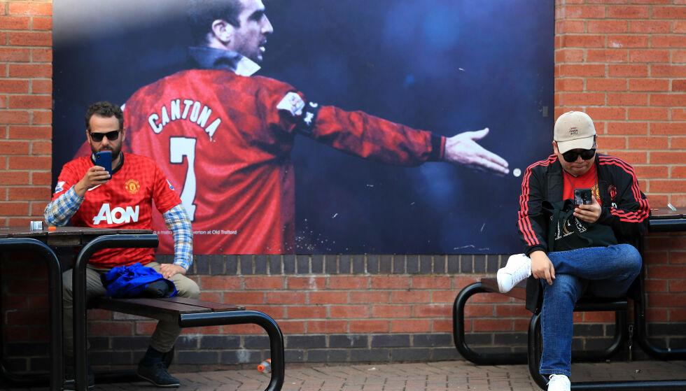 VIL ALLTID BLI HUSKET: Eric Cantona på en plakat på utsiden av Old Trafford, hvor to United-supportere sitter. Foto: NTB scanpix