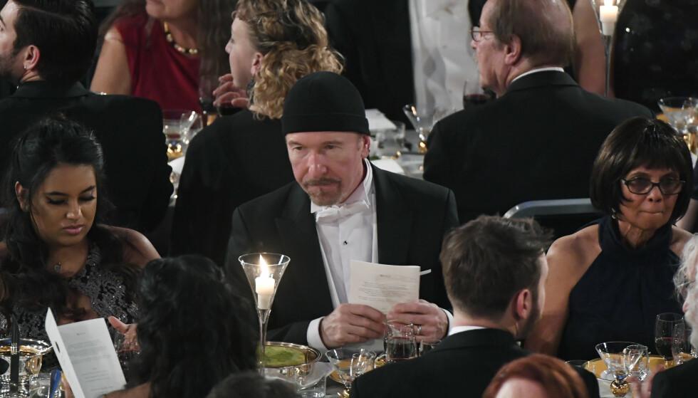 SKILLER SEG UT: Midt i bildet sitter U2s gitarist, The Edge. Han ble invitert til den storslåtte Nobelfesten i Stockholm mandag kveld, og stilte opp i dette antrekket. Det er det ikke alle som setter like stor pris på. Foto: NTB scanpix