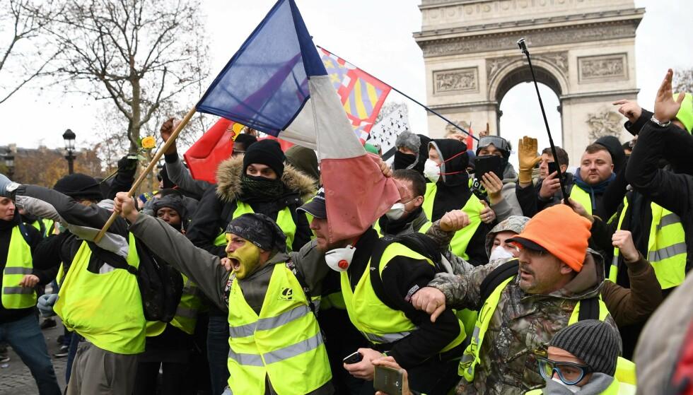 HAR SKAPT OVERSKRIFTER: Demonstranter iført de nå berømte gule vestene foran Triumfbuen i Paris tidligere i desember. Foto: Eric Feferberg / AFP Photo / NTB Scanpix