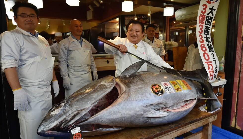 STOLT: - Den er av beste kvalitet, sa sushimagnaten Kiyoshi Kimura da han poserte med rekordfisken på fiskeauksjon i Tokyo. Foto: Kazuhiro Nogi / AFP / NTB scanpix