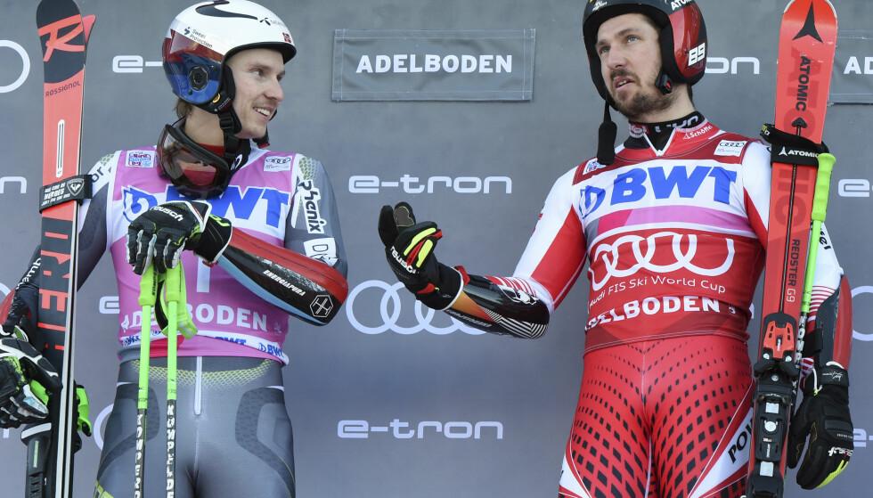 ET VANLIG SYN: Henrik Kristoffersen og Marcel Hirscher diskuterer alpint på et podium. Foto: NTB