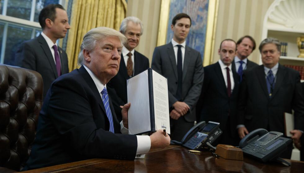 MUNNKURVREGELEN: 23. januar 2017, omgitt av menn i dress, signerte Donald Trump det som på folkemunne refereres til som Global Gag Rule. Foto: Evan Vucci / AP / NTB Scanpix