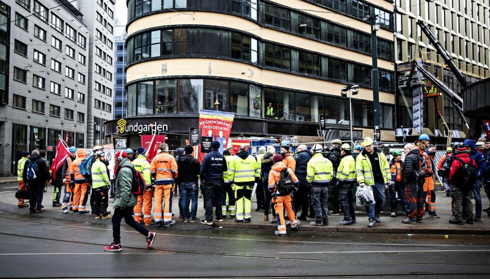 LUNSJPAUSE: Flere av bygningsarbeiderne ved The Hub brukte lunsjpausen sin på å få med seg demonstrasjonen utenfor hotellet som åpnes neste måned. Foto: Nina Hansen