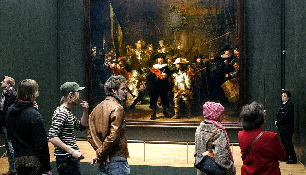 MESTERVERK: Publikum ser på Rembrandt van Rijns berømte Nattevakten i Amsterdams Rijskmuseum. Maleriet skal restaureres for åpen scene i Amsterdam senere i år. Foto: AFP / NTB scanpix