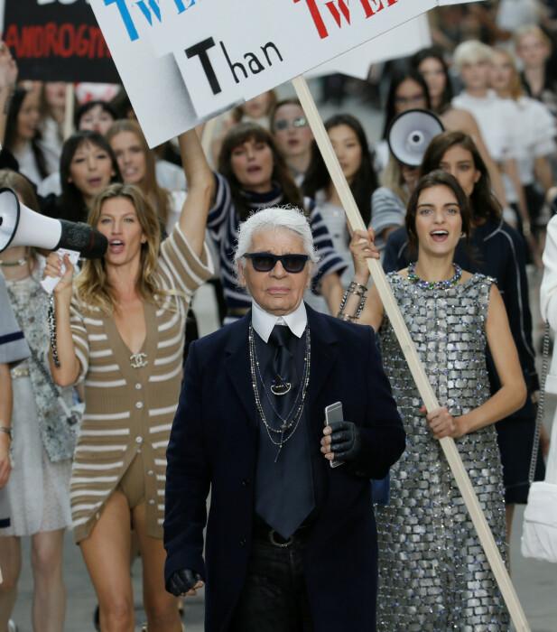 KREATIV: Da Chanel viste sin ready to wear-kolleksjon i 2014, ble den avsluttet av en rekke modeller med protestplakater på catwalken. Lagerfeld gikk foran i spissen, og stuntet skapte store overskrifter verden over. Foto: Reuters / NTB scanpix