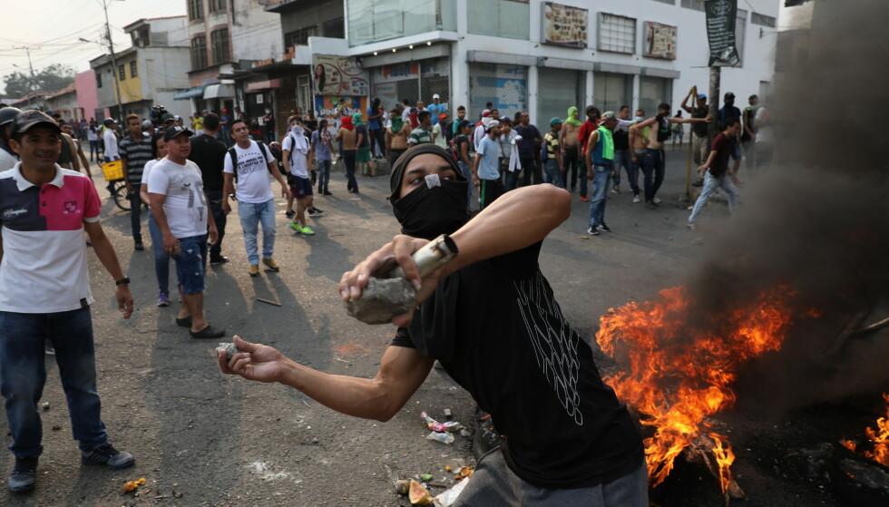 SAMMENSTØT PÅ COLOMBIA-GRENSA: Venezuelas nasjonalgarde brukte tåregass for å åpne ei grensebru barrikadert av regimemotstandere nær Venezuelas grense til Brasil i dag. Demonstranter kastet stein og trillet brennende bildekk. Foto: NTB Scanpix/AP/Rodrigo Abd