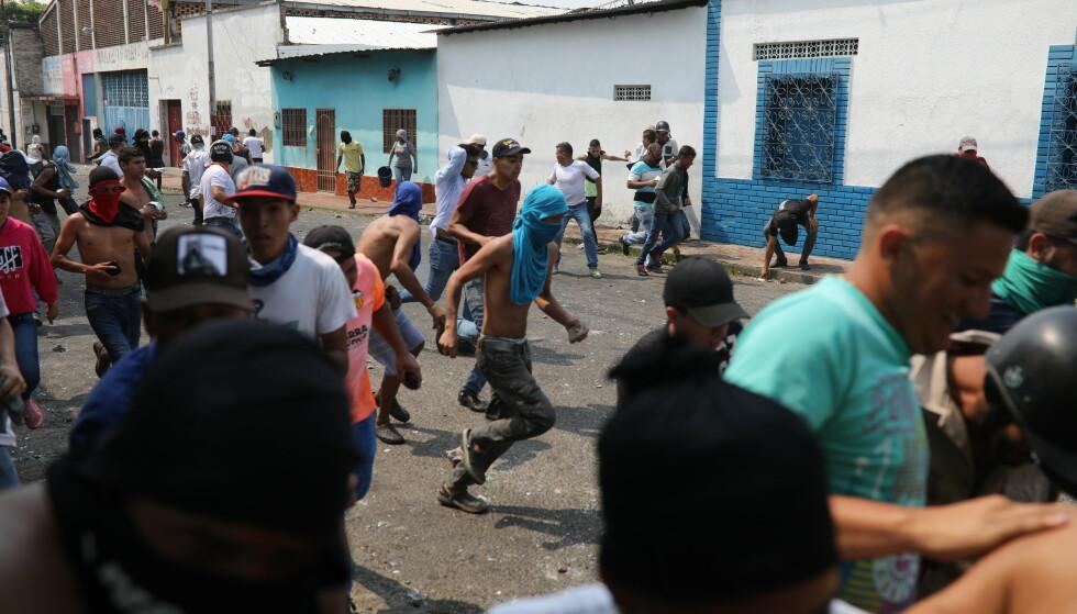 LØPER FOR LIVET: Opposisjonstilhengere løper under et sammenstøt med Den bolivarianske nasjonalgarden til Venezuelas president Nicolas Maduro i byen Ureña nær Colombia. Foto: NTB Scanpix/AP/Rodrigo Abd