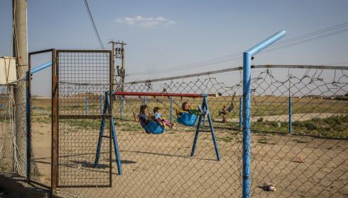 USIKKER FRAMTID: Noen barn svinger seg på huskene som er satt opp inne i en flyktningleir for IS-kvinner og barn i et kurdisk-kontrollerte område i det nordlige Syria. Foto: The New York Times / Scanpix