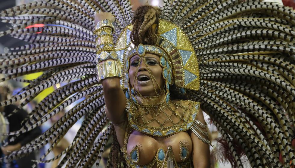 FJÆR OG GULL: Glitter, glamour, heftige rytmer og frekke kostymer er vanlige ingredienser under den årlige karnevalsparaden i Sao Paulo i Brasil. Andre Penner / NTBscanpix.