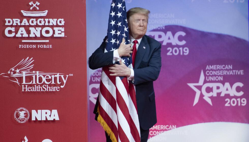KLAMRER SEG TIL FLAGGET: Donald Trump under et møte med konservative velgere i Maryland, lørdag. Foto: NTB Scanpix
