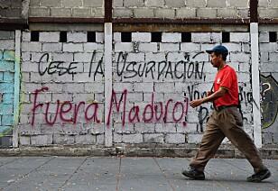 FORSVINN: En mann går forbi en grafitti der det står at Maduro bør forsvinne i hovedstaden Caracas. Det er forventet store demonstrasjoner i Venezuela i dag. Foto: Federico Parra / Afp / Scanpix