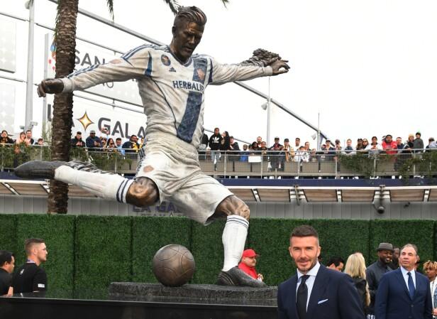 DEN EKTE STATUEN: Her poserer David Beckham foran den ekte statuen av ham - en versjon han var fornøyd med. Foto: AFP.