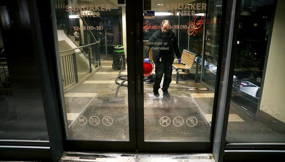 ÅSTEDET: Det var innenfor inngangsdøren at en person ble knivstukket på Sandaker Senter onsdag kveld. Her vasker personell bort de siste blodsporene. Foto: Christian Roth Christiansen