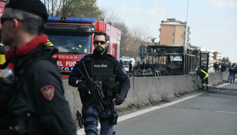 NEDBRENT: Brannfolk og politi på plass ved vraket av den utbrente bussen ved San Donato Milanese utenfor Milano onsdag. En 13-åring varslet om hendelsen. Foto: Daniele Bennati / AP / NTB scanpix