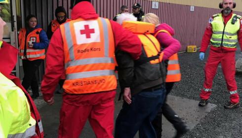 Evakuerte passasjerer ankommer idrettshallen. Røde Kors og nødetater er på plass. Foto: Røde Kors