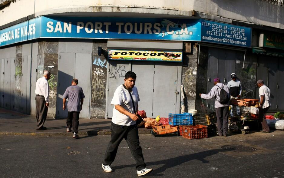 KRISE: Butikkene i Caracas, Venezuela holdt i går fortsatt stengt, etter at en 24 timers strømstans mandag ble utvidet. Det er andre gang på kort tid at strømmen stenges, ogn desperasjonen sprer seg. Artikkelforfatterne mener krisen eskalerte da Juan Guaidó erklærte seg som president. Foto: Cristian Hernandez / AFP / NTB Scanpix