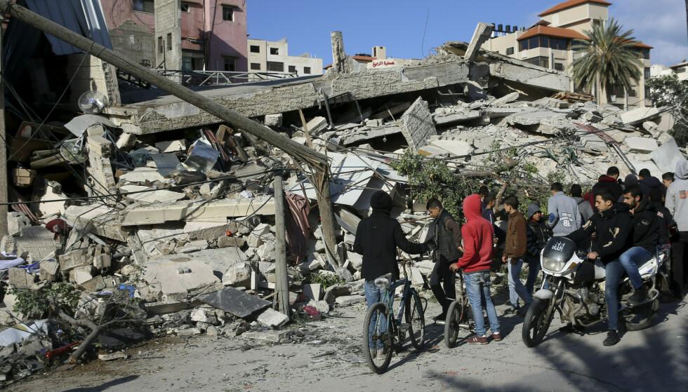 Palestinere ser på ruinene av en bygning som ble ødelagt i israelske luftangrep på Gazastripen tidligere denne uken. Foto: AP / NTB scanpix