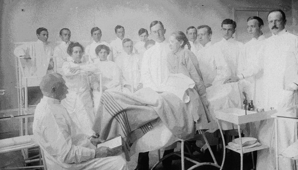 STUDIE: Kvinne studeres av en gruppe leger ved Rikshospitalet i 1899, på «Hudsygeavdelingen», under overlege og professor Carl Wilhelm Boeck. Foto: Narve Skarpmoe.