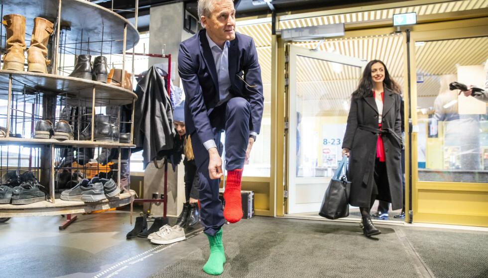 DET NYE AP: Leder Jonas Gahr Støre ikler seg sine røde og grønne raggsokker når han og nestleder Hadia Tajik ankommer Arbeiderpartiets pressekonferanse på Biblo Tøyen tidligere i uka - der det er skoforbud. Foto: Håkon Mosvold Larsen / NTB scanpix