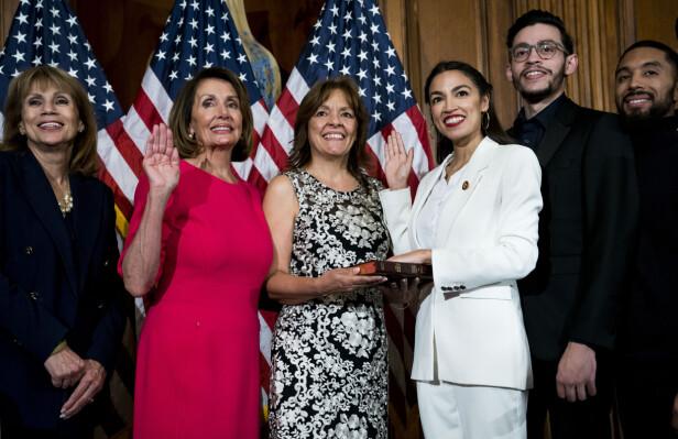 TATT I ED: Alexandria Ocasio-Cortez (i hvitt) tas i ed som kongressrepresentant av speaker Nancy Pelosi (i rosa) i januar. Ocasio-Cortez´ mor Blanca i midten. Broren Gabriel Ocasio-Cortez til høyre. Foto: Doug Mills/The New York Times