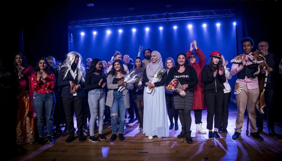 PREMEIEREJUBEL: Shabana Rehman (med blomster), leder av Født Fri, svarer på kritikken fra tre skoleelever etter at hun og Zahid Ali (i midten bak) var med på å blåse liv i Stovnerrevyen. Foto: Stovnerrevyen