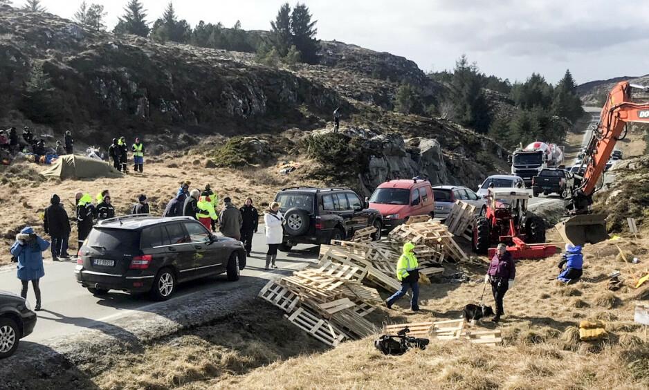 Demonstranter: Politiet har bøtelagt demonstrantenes biler som står langs veien på Frøya. Pallene som ble levert av Gustav Witzøe ble brukt til å hindre anleggstrafikk til å kjøre forbi. Foto: Ronny Teigås / NTB scanpix