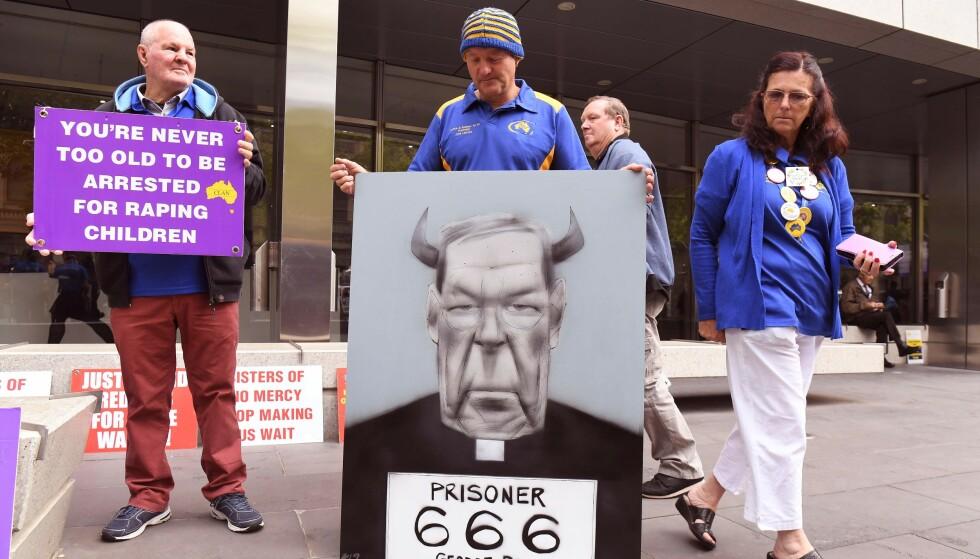 TILSKUERE: Offere for overgrep i kirken holdt opp plakater utenfor retten før straffeutmålingen i saken mot George Pell. Foto: AFP / NTB Scanpix