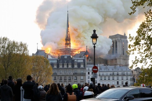 Seen from across the Seine River, smoke and flames rise during a fire at the landmark Notre-Dame Cathedral in central Paris on April 15, 2019, potentially involving renovation works being carried out at the site, the fire service said. (Photo by FRANCOIS GUILLOT / AFP)